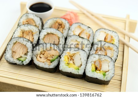 Breaded and teriyaki chicken sushi on bamboo tray against white background - stock photo