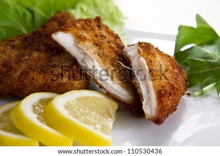 Breaded chicken breast with lemon and salad - stock photo