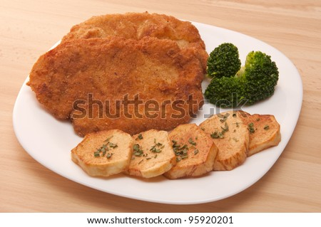 Breaded chicken fillet with potatoes and broccoli - stock photo