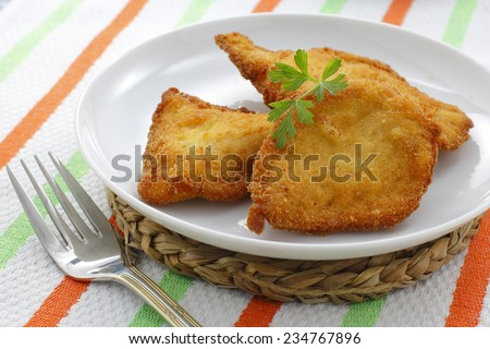breaded chicken fillets, served at the table - stock photo