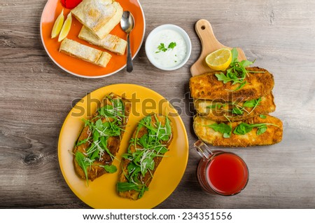 Breaded eggplant parmesan and arugula, fresh limonade from red orange and cheese dip - stock photo