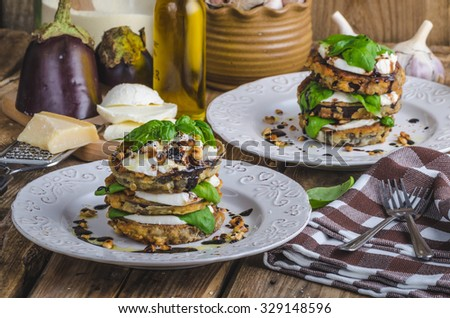 Breaded eggplant with nuts, mozzarela, basil and balsamic reduction, delicious vegetarian meal - stock photo