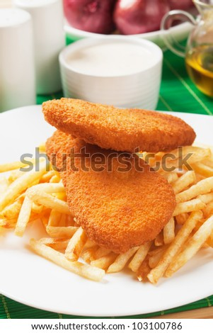 Breaded fish and french fries on white plate