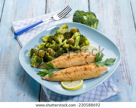 breaded fish with broccoli and olives - stock photo