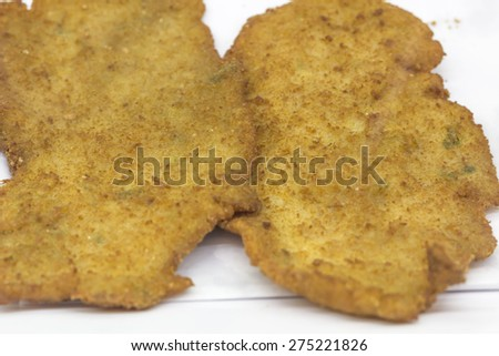 Breaded fried chicken cutlets on platter on display at restauant - stock photo