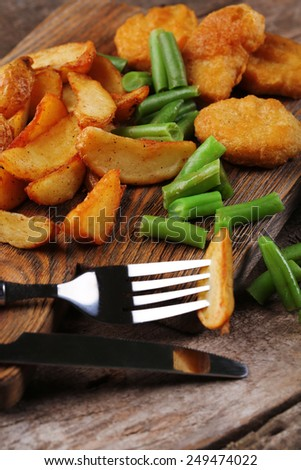 Breaded fried chicken nuggets and potatoes with asparagus on catting board and wooden planks background - stock photo