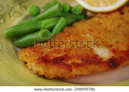 Breaded fried fish fillet and potatoes with asparagus and sliced lemon on green plate background - stock photo