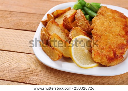 Breaded fried fish fillet and potatoes with asparagus and sliced lemon on plate and wooden planks background - stock photo