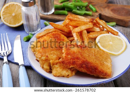 Breaded fried fish fillets and potatoes with asparagus and sliced lemon on plate and wooden planks background - stock photo