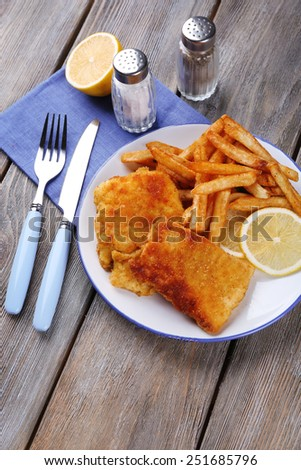 Breaded fried fish fillets and potatoes with with sliced lemon and cutlery on plate and wooden planks background - stock photo
