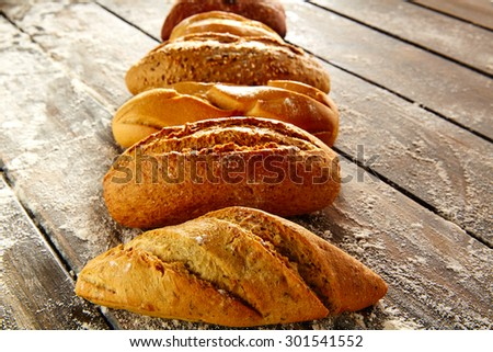 Breads varied in a row on rustic wood table with wheat flour - stock photo
