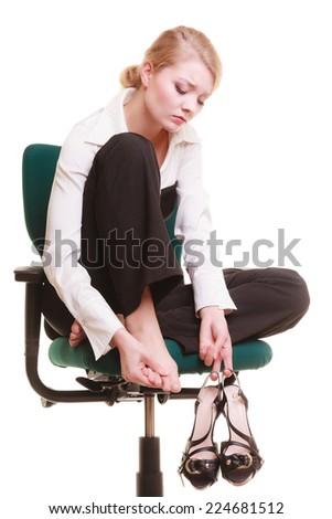 Break from work. Tired businesswoman with leg pain. Young woman massaging her feet on chair isolated on white. - stock photo