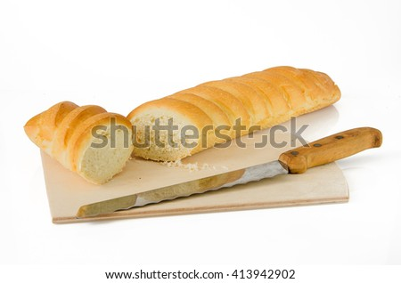 break large sweet baguette with knife on wooden cutting board - stock photo