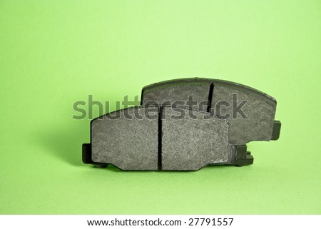 Break pads on green background with shadow - stock photo