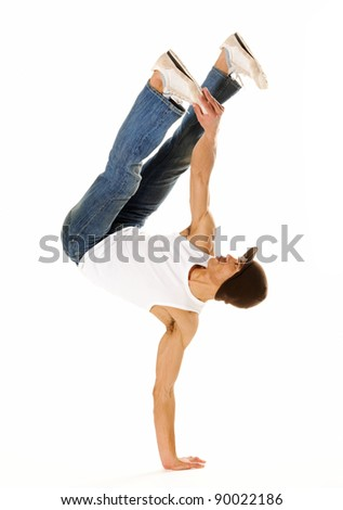 breakdancer does moves while performing a hand stand - stock photo