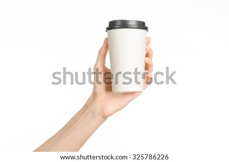 Breakfast and coffee theme: man's hand holding white empty paper coffee cup with a brown plastic cap isolated on a white background in the studio, advertising coffee  - stock photo
