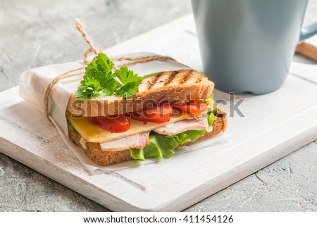Breakfast and Lunch - Sandwich and Coffee on cutting board - stock photo