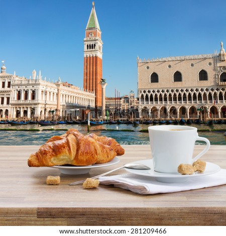 Breakfast at Venice - cup of coffee with croissant by San Marco waterfront, Italy - stock photo