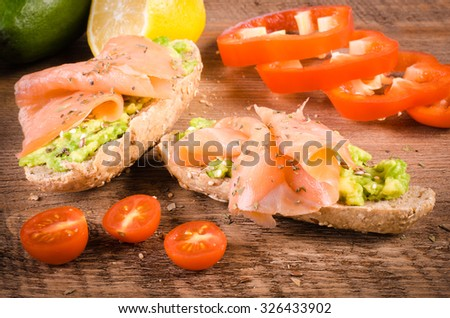 Breakfast:  avocado toast with vegetables On Wooden Background.