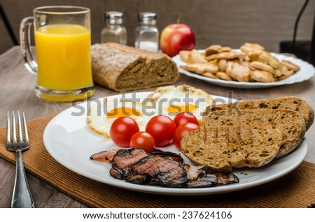 Breakfast- bacon, sausage, bread and eggs, orange juice and christmas gingerbread back - stock photo