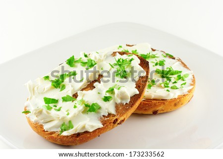 Breakfast bagel with cream cheese and topped with fresh Italian parsley.