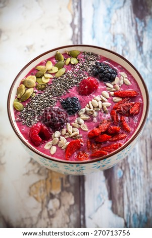 Breakfast berry smoothie bowl topped with goji berries,raspberry, blackberry, pumpkin, sunflower and chia seeds. - stock photo