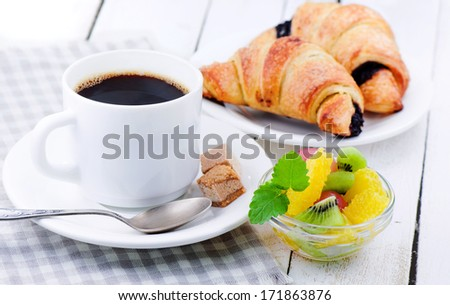 Breakfast. Black coffee, fresh, crackling croissant with chocolate and fruit - stock photo