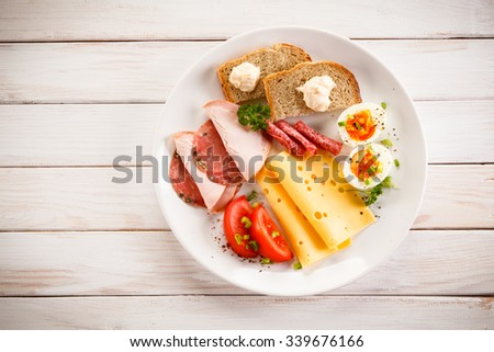Breakfast - boiled egg, bacon, cheese and vegetables  - stock photo