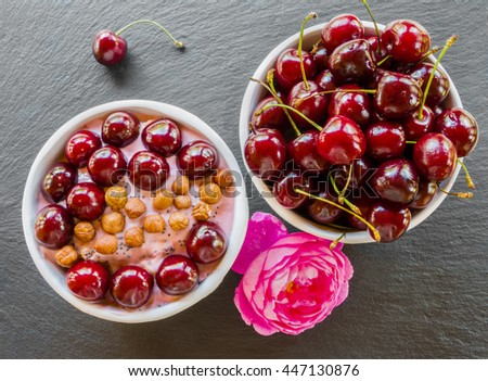 Breakfast bowl with yogurt,  granola or muesli or oat flakes, fresh cherries and nuts. Black stone background, pink rose flower. Top view. - stock photo