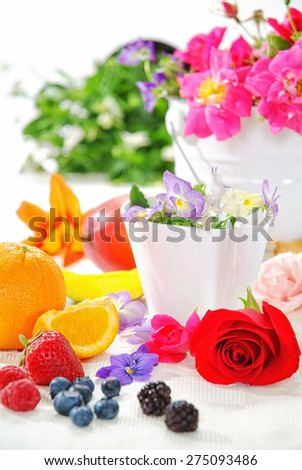 Breakfast brunch table fresh and sunshine morning, flowers, rose, viola, pink strawberry, orange, blueberry, blackberry, pear, pineapple, on yellow tablecloth and wood board, white bowl et rose petal.