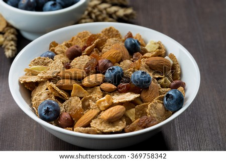 breakfast cereal flakes with blueberries and nuts on a dark wooden table, closeup, horizontal - stock photo
