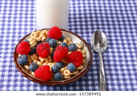 Breakfast cereal with berries on a blue tablecloth
