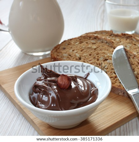 Breakfast, chocolate creme with whole wheat bread and milk - stock photo