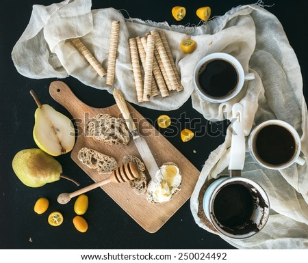 Breakfast / coffee break set: a pot of coffee, cups, waffle rolls, kumquats, pears, baguette slices with butter cream and honey on a rustic wooden board over a black backdrop. Top view - stock photo