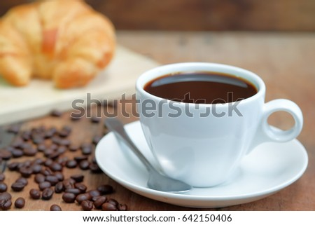 Breakfast coffee croissant on wooden table and roasted coffee bean