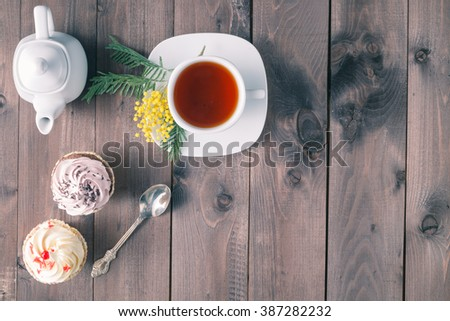 Breakfast concept. Two cupcakes on dark wooden table, top view - stock photo