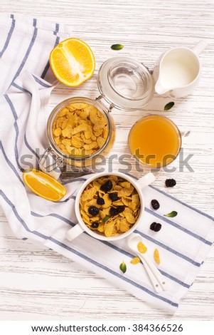 Breakfast concept with corn flakes, milk, dry cranberry and orange juice over wooden table - stock photo
