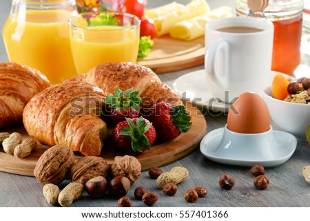 Breakfast consisting of croissants, coffee, fruits, orange juice and jam. Balanced diet.