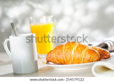 breakfast croissant, glass of orange juice and cup of hot drink