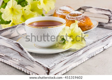 Breakfast Danish pastry and cup of tea on vintage  serving tray. Sweet cinnamon rolls and tea cup with yellow flowers. Breakfast tea with sweet pastry. - stock photo
