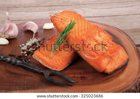 breakfast delicious portion of fresh roast salmon fillet with dry spices garlic and rosemary on wooden plate with black forged handmade fork healthy food diet cooking concept - stock photo