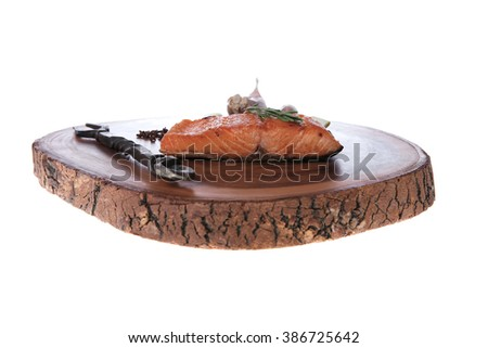 breakfast delicious portion of fresh roast salmon fillet with dry spices garlic rosemary wooden plate black forged handmade fork healthy food diet cooking concept isolated white background empty space - stock photo