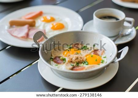 Breakfast egg dish served with fried egg, ham, orange juice, delicious. - stock photo