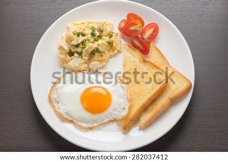 breakfast, fresh fried egg and scrambled egg with bread - stock photo