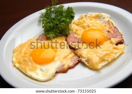 Breakfast fried eggs with ham and cheese on a plate - stock photo