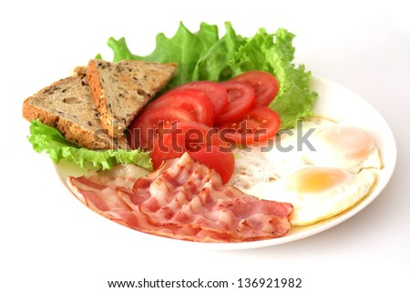 Breakfast from bacon and egg with lettuce leaves and tomatoes. Isolated on a white background.