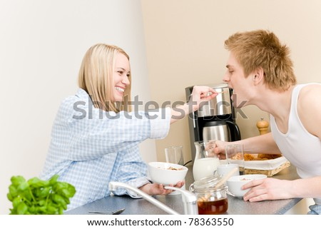 Breakfast happy couple  woman feed cereal to man in kitchen