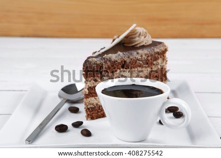 breakfast hot coffee mug and cream chocolate layer cake decorated with white chocolate slice and cream flower on white plate over wood - stock photo