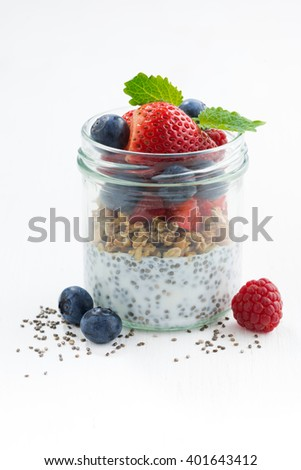 Breakfast in a glass jar, chia with berries and oat flakes on white table, vertical, closeup - stock photo