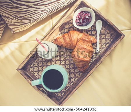 Breakfast in bed. Fresh croissants with coffee.